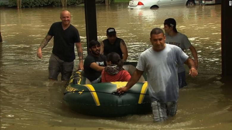 Los vecinos jalan Ahmed Sharma y su esposa , Emily, a la seguridad después que su complejo de apartamentos en Klein , Texas se inundo .
