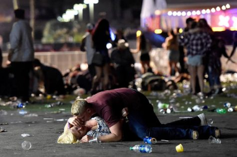 LAS VEGAS, NV - OCTOBER 01:  A man lays on top of a woman as others flee the Route 91 Harvest country music festival grounds after a active shooter was reported on October 1, 2017 in Las Vegas, Nevada. A gunman has opened fire on a music festival in Las Vegas, leaving at least 2 people dead. Police have confirmed that one suspect has been shot. The investigation is ongoing. (Photo by David Becker/Getty Images)