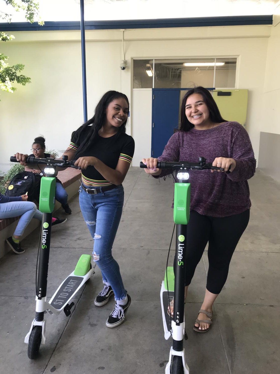 Alexis Smith, left, and Miki Lopez, right, pose with two Lime scooters September 12, 2018 in front of the Main Gym. Recently, students have been riding these scooters to school often. (Nancy Quintana / Lincoln Lion Tales)