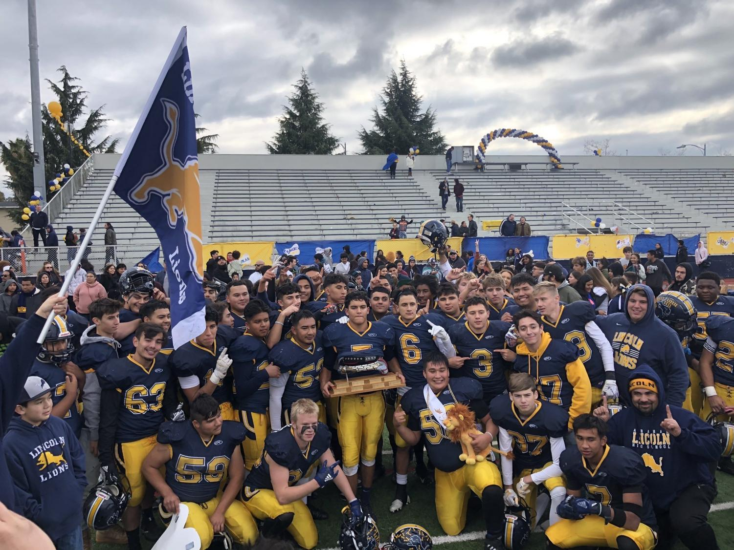 Lions celebrating after their win against San Jose High School with the big bone trophy. (Adrian Uribe)