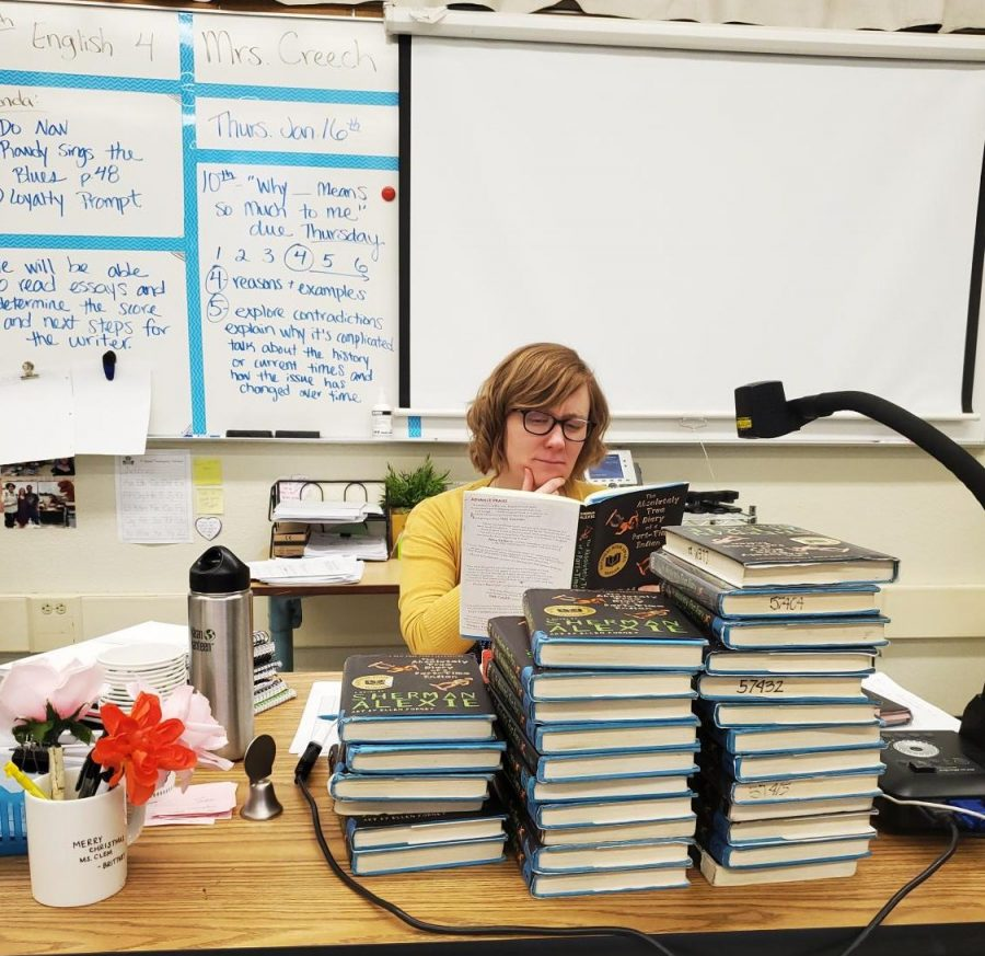 Mrs. Creech alongside a mountain of books.  (Gio Quezadas/ Liontales)